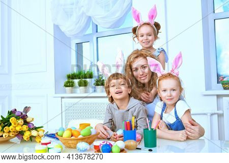Happy mother with her three children are preparing for Easter. Easter holiday. Loving family concept.