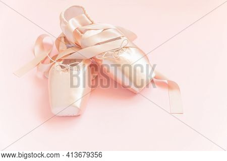 New Pastel Beige Ballet Shoes With Satin Ribbon Isolated On Pink Background. Ballerina Classical Poi