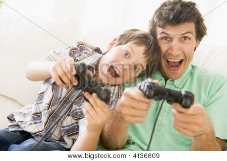 Man And Young Boy With Video Game Controllers Smiling