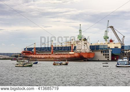 Large General Cargo Ship For Transportation Import Export Goods Moored In The Harbor And In The Proc