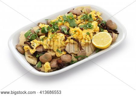 iraqi breakfast; boiled dried broad beans and scrambled eggs over pieces of flatbread