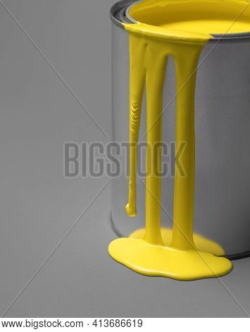 Close-up Of A Metal Can And Yellow Paint Dripping On It. Yellow Paint Drip And Puddle On A Gray Back