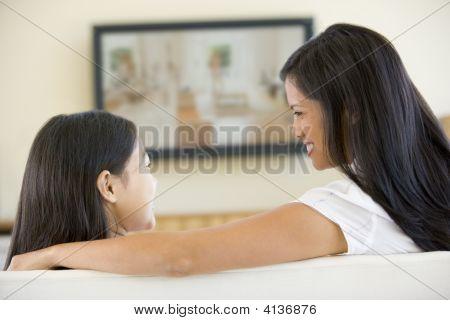 女性と少女リビング ルーム フラットで画面のテレビの笑みを浮かべて