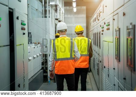 Technical Worker With Engineer Working And Checking In Control Room Power Plant At Industry Factory.