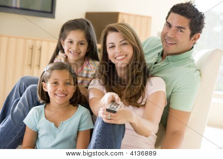 Families In Living Room With Remote Control Smiling