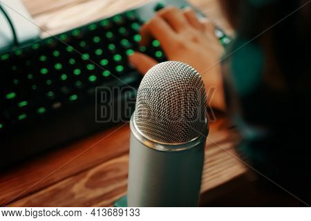 Man With Headphones Is Typing On The Keyboard And Podcasting With Retro Old Microphone. Radio Show O