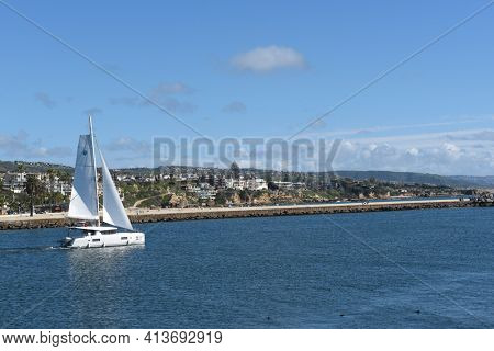 NEWPORT BEACH, CALIFORNIA - 22 FEB 2017: A private yacht sails through the entrance channel in Newport Beach with Corona del Mar in the background.