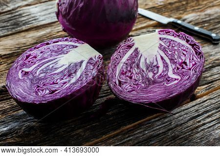 Red cabbage on rustic looking wood with knife