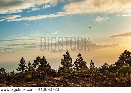 Paraglider Flying In Dramatic Orange Sunset With Scenic Clouds. Brown Desert Rocks And Pine Trees. P