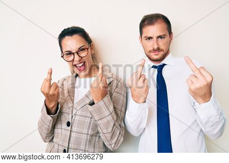 Beautiful couple wearing business clothes showing middle finger doing fuck you bad expression, provocation and rude attitude. screaming excited