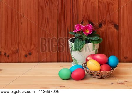 Easter Concept. Сolorful Easter Eggs And Primula Flower On Wooden Table. Selective Focus. View With