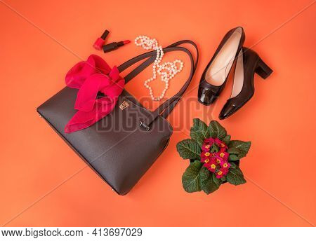 Gray Leather Bag, Black Shoes, Cosmetics, Necklace And Primrose Flower On Orange Background. Top Vie
