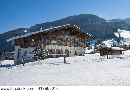Leogang, Austria - January 29, 2014: Austrian Traditional Tyrolean Family House In The Snow. Alpine