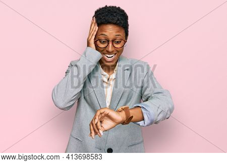 Young african american woman wearing business clothes looking at the watch time worried, afraid of getting late