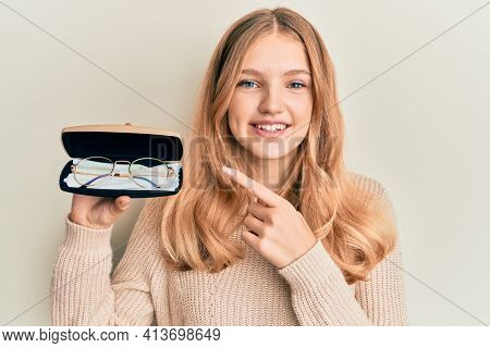 Beautiful young caucasian girl holding glasses in eyewear case smiling happy pointing with hand and finger