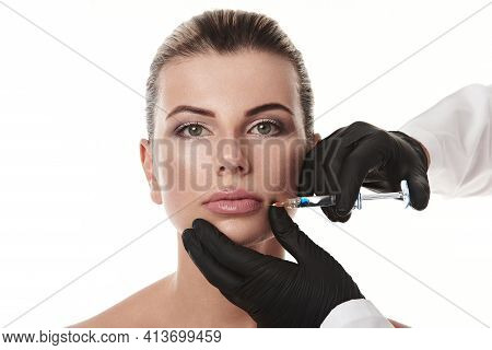 Closeup Of Attractive Woman's Face Isolated On White Background And Beauticians Hands In Gloves Maki