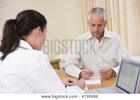 Doctor With Laptop And Man In Doctor'S Office