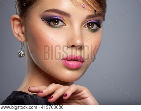 Portrait of a beautiful woman with bright makeup. Closeup female face with purple eye make-up. Pretty,  girl with violet nails near face. Stylish fashion model with a short slick hair