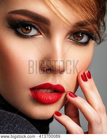 Beautiful brunette girl with red lips and short hair. Pretty young  woman with red nails. Closeup portrait of a model with bright makeup on a face. Attractive female posing at studio.
