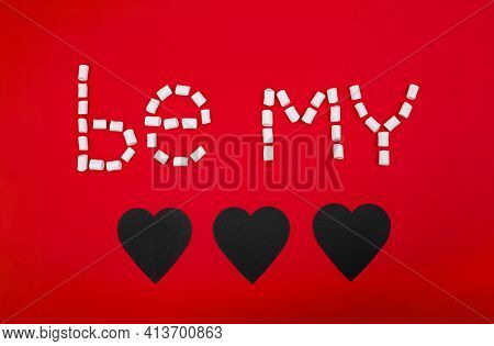 Text Made By White Marshmallows On Red Background With Three Hearts