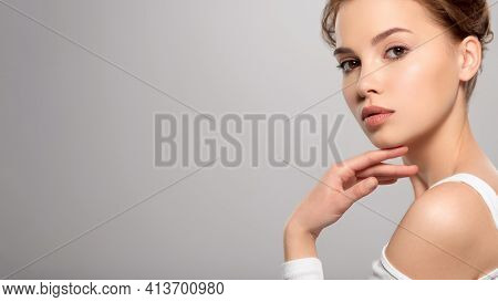 Beautiful face of young caucasian woman with perfect healthy skin, isolated.   Pretty white model caring of face. Beauty treatment concept. Skin care concept.