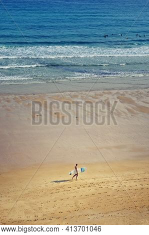 View On The Beach From The Rock Above. Surfer Walks With A Surfboard. Ocean And Surfers In The Backg