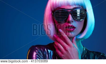 Stylish blonde in shiny dress and sunglasses with stresses. Closeup face  of beautiful  fashionable woman in white wig. Art portrait  of  an young attractive model. Fantasy style. Glamour fashion girl
