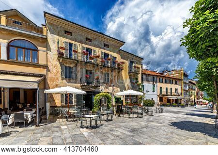 View of promenade along old houses and outdoor restaurant in Cannobio - small town in Piedmont, Italy on the shores of Lake Maggiore.