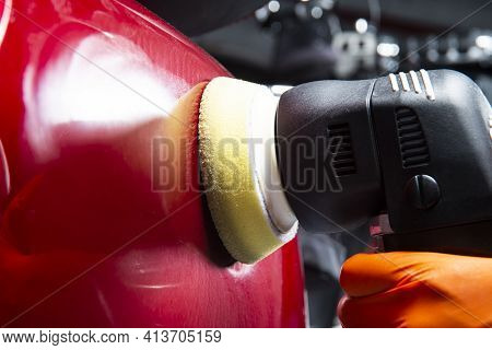 Buffing And Polishing Car. Car Detailing. Man Holds A Polisher In The Hand And Polishes The Red Car.