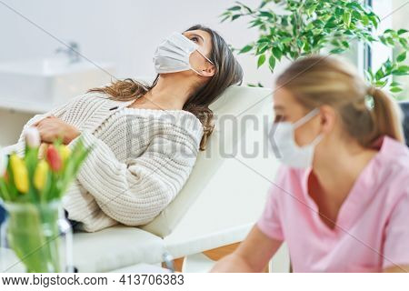 Professional psychiatrist consulting her patient and making notes both in masks