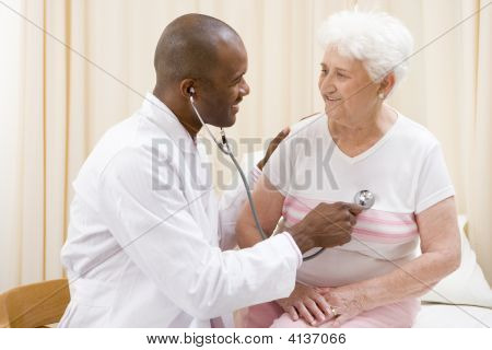 Doctor Giving Checkup With Stethoscope To Woman In Exam Room Smiling
