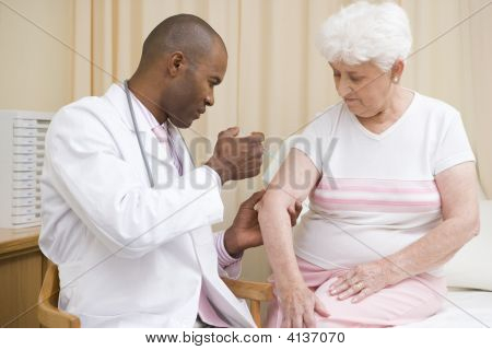 Doctor Giving Needle To Woman In Exam Room