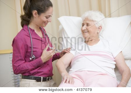 Doctor Giving Needle To Woman In Exam Room Smiling