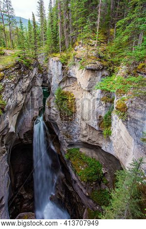 The Canadian Rockies. Cool cloudy day. Powerful waterfall in a picturesque gorge Maligne Canyon. Cool cloudy day. The sheer canyon walls and the seething icy water below.
