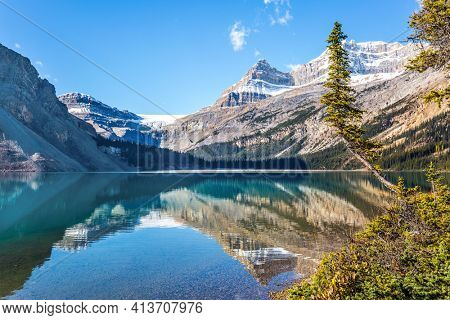 Rocky Mountains, Canada. Glacial lake Bow with clear azure water. Mountains are reflected in the smooth water of the lake. Cold sunny autumn day.