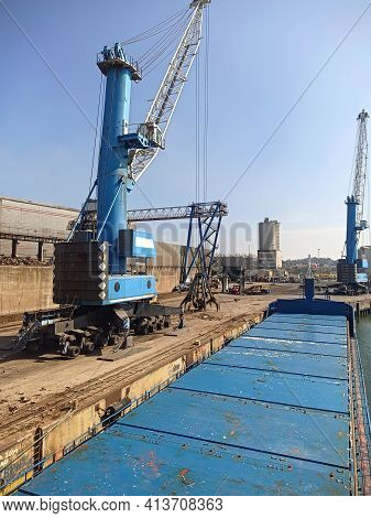 Crane Manipulator With Gripper In The Port For Loading Scrap Metal. Equipment In The Port For Loadin