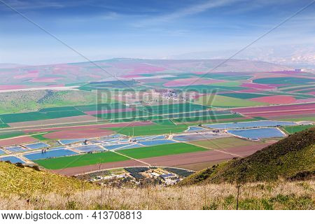 Jezreel Valley in the Lower Galilee. Warm winter in Israel. Picturesque agricultural fields cover the entire valley. Aerial view