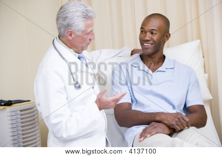 Doctor Giving Smiling Man Checkup In Exam Room