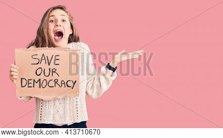 Young beautiful blonde woman holding save our democracy banner celebrating victory with happy smile and winner expression with raised hands