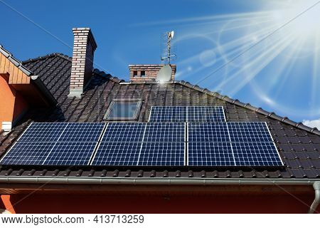 Solar Panels On The Roof Of A Beautiful Modern Home. Sunrays