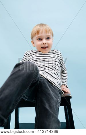 Playful Little Blond Boy Sitting On A Stepping Stool, Reaching Camera With A Leg
