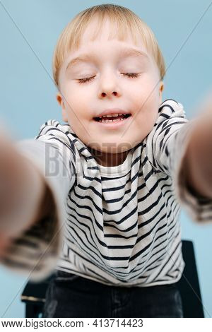 Funny Blond Boy Sitting On A Stepping Stool. Over Blue Background