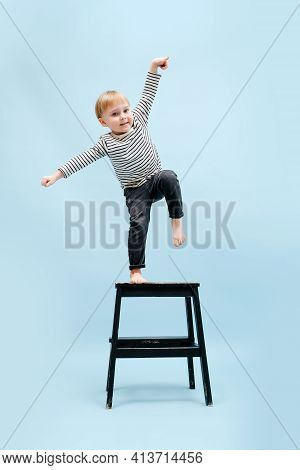 Agile Blond Boy Balancing On One Foot On A Stepping Stool. Over Blue Background