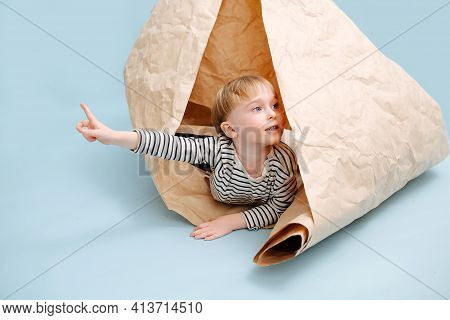 Playful Blond Boy Lying In A Rolled Packing Paper. Over Blue Background