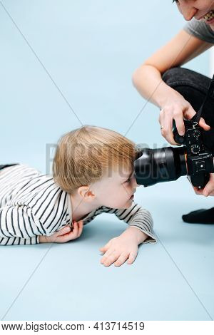 Funny Blond Boy Lying On The Floor, Ramming Camera Objective With His Forehead.