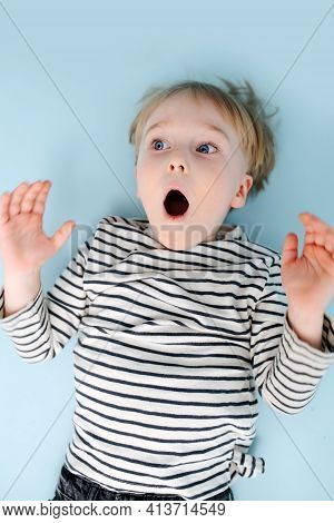 Grimacing Blond Boy Lying On The Floor With Wide Open Mouth. Over Blue Background.