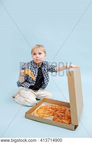 Squimish Blond Boy Sitting On A Floor With Pizza Slice In Hand, Holding Box Lid