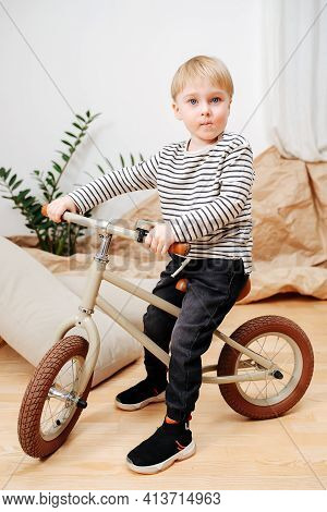 Handsome Blond Boy Sitting On A Small Beige Two Wheel Bike Inside A Room