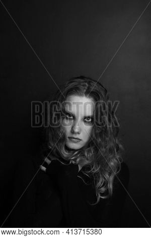 Vintage style black and white portrait of beautiful young girl with long curly hair and smoky eye makeup