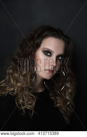 Vintage style portrait of beautiful young girl with smoky eye makeup and fancy ring earrings, selective focus, grainy